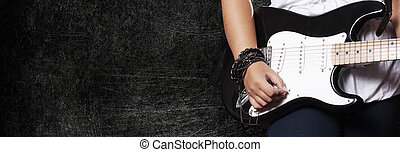 Closeup of girl playing on guitar on dark grunge background