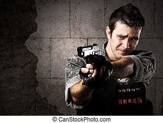 soldier aiming - portrait of young soldier aiming with gun...