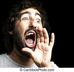 young man shouting against a black background
