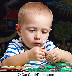 Focusing on playing - Toddler boy playing with a colorful...