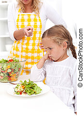 Training for a healthy eating habit - Mother training a...