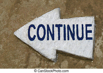Continue - A continue sign on a white rock shaped as an...