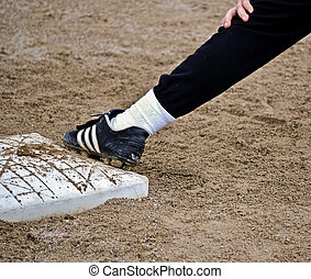 baseball player on base - Baseball player with foot on first...