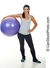 Happy fitness trainer woman holding pilates ball and smiling...