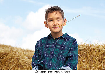 Boy on hay - Happy lad looking at camera in countryside