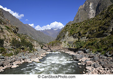 Wild Urubamba river flowing through valley with high snow...