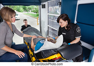 Senior in Ambulance - Ambulance workers caring for a senior...