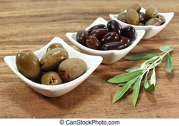 Olives - different varieties of olives with olive branch