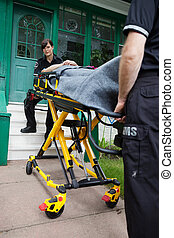 Ambulance House Visit - Ambulance workers with a stretcher...