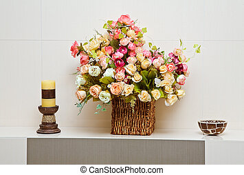 Composition with artificial flowers bouquet in wattled vase