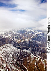 Aerial view of snow-covered mountains under cloudy blue sky
