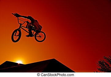 Bmx rider at jump against sky at sunset.