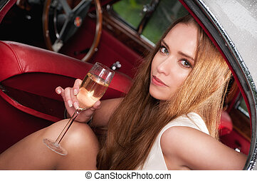 drinking champagne - elegant woman in an old car drinking a...