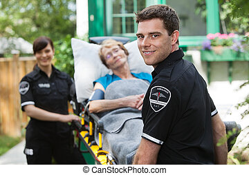 Ambulance Worker with Patient - Male ambulance professional...