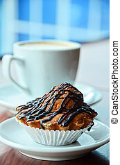 muffins - Chocolate muffins with and coffee cup on orange...