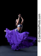beauty dancer posing in dark with fly purple veil
