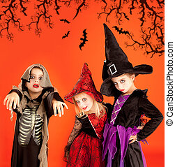 Halloween group of children girls costumes on orange...