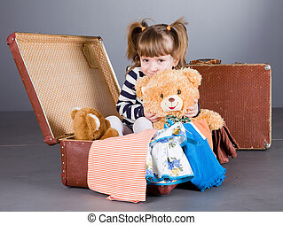 girl joyfully sits in an old suitcase - four-year girl...
