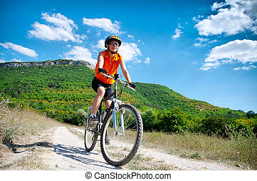 girl rides a bicycle - young athletic girl rides a bicycle...