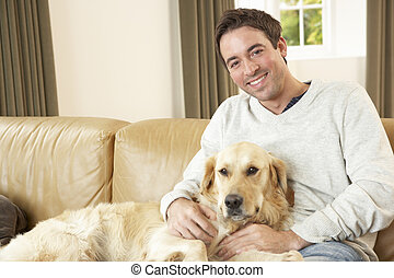 Young man with dog sitting on sofa