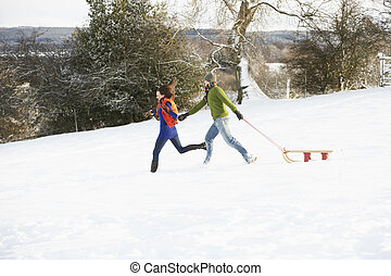 Teenage Couple Pulling Sledge Across Snowy Field