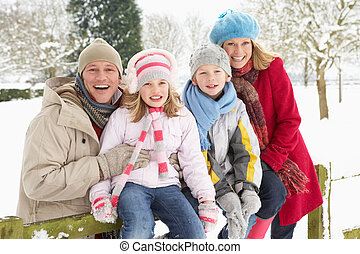 Family Sitting In Snowy Landscape