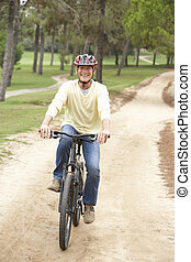 Senior man riding bicycle in park