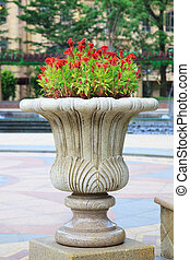 Ornamental stone flowerpot in garden.The flower on vase is...