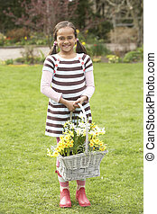 Girl Holding Basket Of Daffodils In Garden