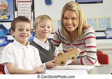 Two Male Primary School Pupils And Teacher Working At Desk...
