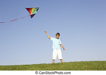 Young boy poses with kite in a field