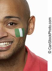 Young Male Sports Fan With Nigerian Flag Painted On Face