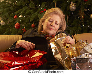 Tired Senior Woman Returning After Christmas Shopping Trip