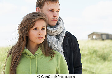 Romantic Young Couple Standing By Dunes With Beach Hut In Distance
