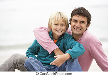 Father And Son Sitting On Winter Beach Together