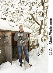 Middle Aged Man Clearing Snow From Path To Wooden Store