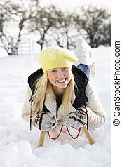 Teenage Girl Riding On Sledge In Snowy Landscape