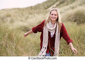 Teenage Girl Walking Through Sand Dunes Wearing Warm Clothing