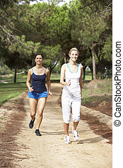Two young women running in park