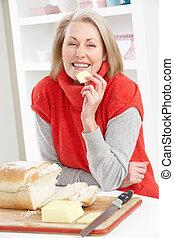Senior Woman Making Sandwich In Kitchen