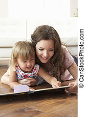 Mother And Daughter Learning To Read At Home