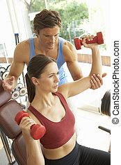 Young Woman Working With Weights In Gym With Personal...