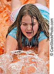 Summer Fun - Girl playing on water slide to cool off in...