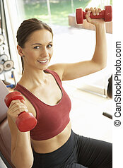 Young Woman Working With Weights In Gym