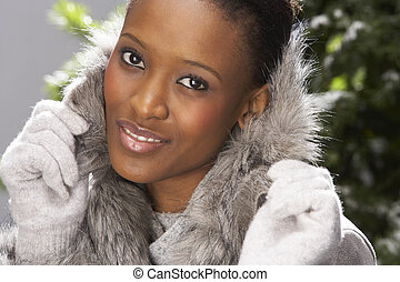 Fashionable Woman Wearing Fur Coat In Studio In Front Of...