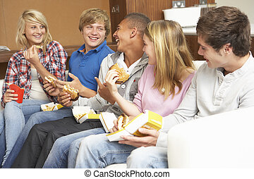 Group Of Teenage Friends Sitting On Sofa At Home Eating Fast...