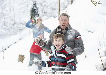 Young Family Having Snowball Fight In Snowy Landscape