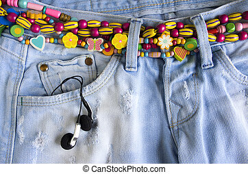 girlish jeans - Close-up of worn blue jeans with headphones...