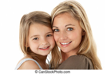 Studio Portrait Of Mother Hugging Young Daughter