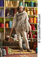 Woman Wearing Knitted Scarf Standing In Front Of Yarn...